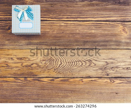 Square Gift Box Wrapped in Blue Plaid Paper with Blue and White Bow on Wooden Background with Copy Space seen from Above - stock photo