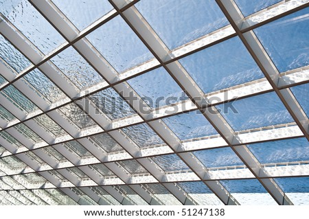 square patterns filled with water on the glass roof of modern building