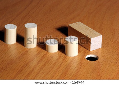 Square peg and a round hole.  Metaphor for a misfit or nonconformist. - stock photo