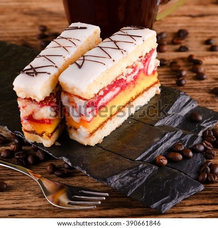 Square photo of two slices of sweet desert with color layers on sugar on the top placed on piece of black stone. Cup of coffee is in background on wooden board with few coffee grains around. - stock photo
