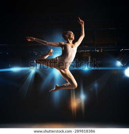 square photo of young blonde ballet dancer in jump on stage in theater - stock photo