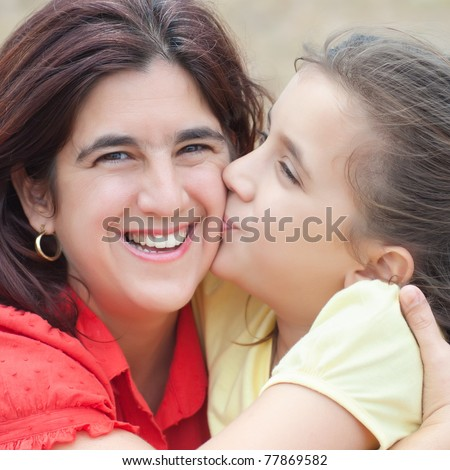 Square portrait of a cute latin girl kissing her beautiful mother with a diffused grass background - stock photo