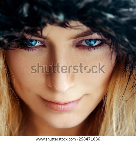 Square portrait of cutie young woman with blond hair and blue eyes in fur hat. Color high contrast photo - stock photo