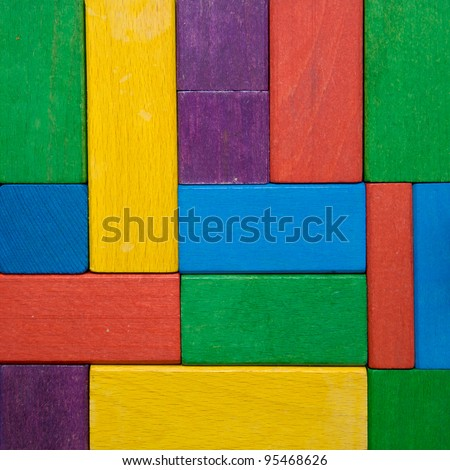 Square shape colorful background in red, yellow, green, purple and blue created of wooden toy blocks. Ready for your design, letters, symbols or logo.