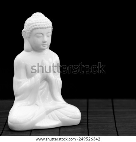 Square shot of a white figure in meditation pose - stock photo