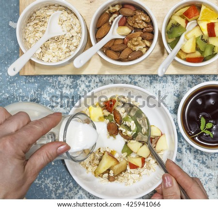 Square shot. Young woman pouring cream or yogurt  in a bowl with fruit salad , notebook. Proper nutrition, diet - stock photo