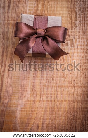 square vintage gift box with brown ribbon on old wooden board with copyspace