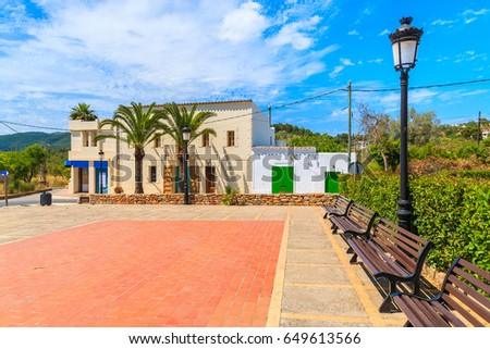 Square with colourful houses and palm trees in Sant Carles de Peralta village, Ibiza island, Spain