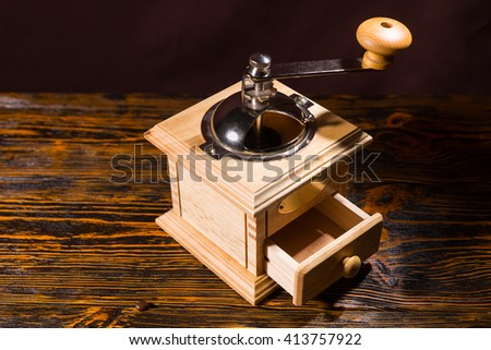 Square wooden coffee grinder with little open drawer and metal handle over table with dark background