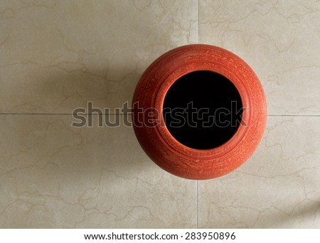 Squares, rectangles and circles. A red clay pot on tiled floor. view from top. Terracotta pot for interior decoration. Geometric lines and patterns. - stock photo