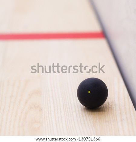 Squash ball with yellow dot - stock photo