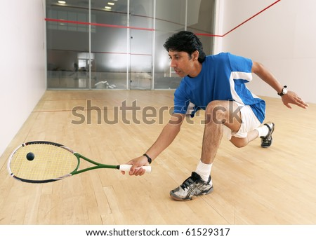 Squash player hiting a drop shot in a squash court.
