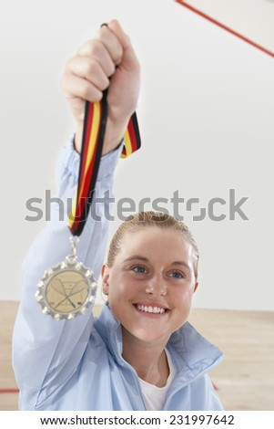 Squash Player Holding Medal - stock photo