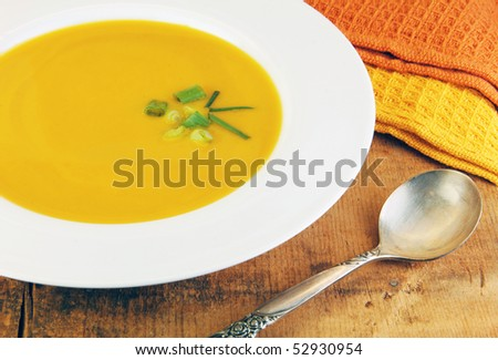 Squash soup  in white bowl with a spoon on a rustic wood table. - stock photo