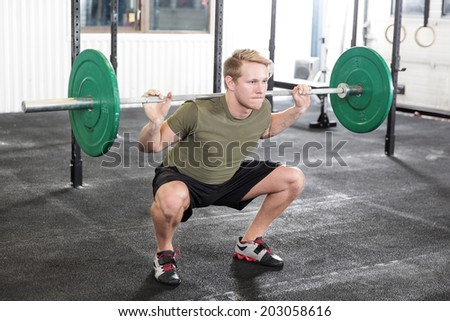 Squat workout at fitness gym center - stock photo