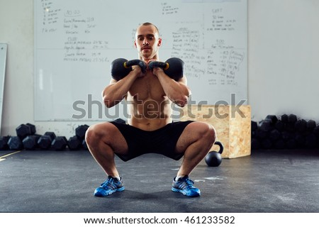 Squats with kettlebells exercise - young athlete doing functional workout at the gym