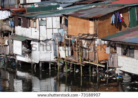 Squatter homes in the Philippines - shacks in shanty town along heavily polluted Paranaque river in Manila. - stock photo