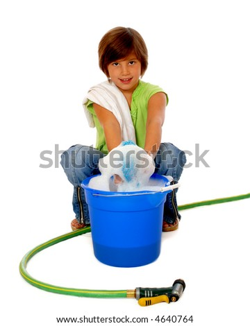 Squatting elementary girl with cleaning supplies pulling sponge from a bucket of sudsy water.  Isolated on white.