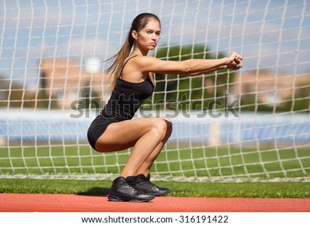 squatting.warming-up.young beauty girl do exercises at the stadium - stock photo