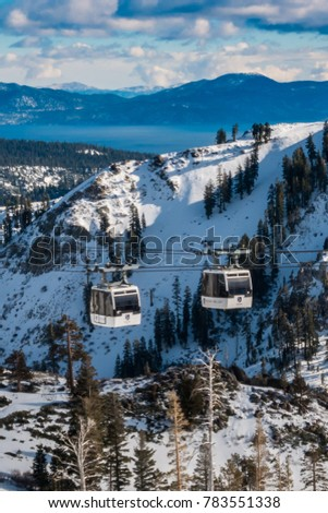 Squaw Valley, California - December 20, 2017:Two gondolas pass each other, at Squaw Valley Ski Resort, in the Sierra Nevada Mountains of California, home to 1960 Winter Olympics, with view Lake Tahoe.