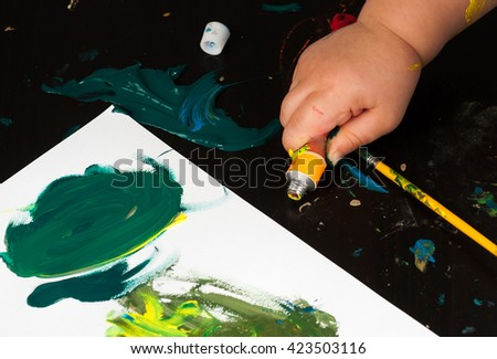 Squeezeing tube of acrylic paint by child - stock photo