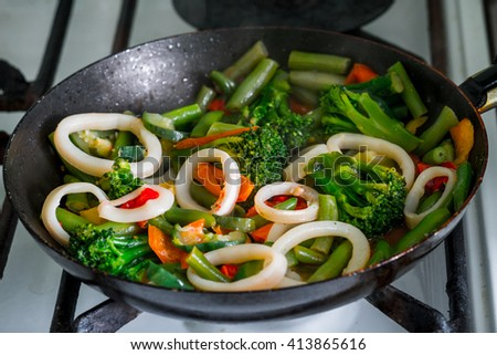 squid and broccoli with beans and fresh vegetables stir-fried in a skillet for a wholesome and delicious food - stock photo