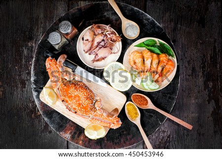 Squid,jumbo crab and shrimp on dark background - stock photo