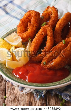 squid rings fried in breadcrumbs close-up on a plate with ketchup and lemon. Vertical