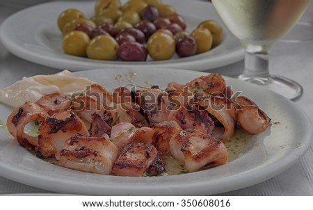 Squids served as a meal for the restaurant with herbs as a side dish - rustic wooden background - calamari squid fresh seafood - stock photo