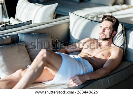 Squinting young, handsome man relaxing on a couch in a hotel with a towel wrapped around his hips - stock photo