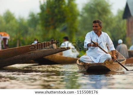 SRINAGAR, INDIA - JULY 11: A Kashmiri man rows by the remainder of the morning floating market on Dal Lake, a major tourist attraction, in Kashmir on July 11, 2009 in Srinagar, India - stock photo