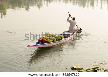SRINAGAR, INDIA - JULY 07, 2015 : Lifestyle in Dal lake, local people use 'Shikara', a small boat for transportation in the lake of Srinagar, Jammu and Kashmir state, India - stock photo
