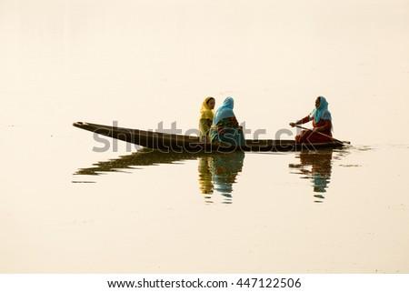 SRINAGAR, INDIA - JULY 07, 2015 : Lifestyle in Dal lake, local people use Shikara, a small boat for transportation in the lake of Srinagar, Jammu and Kashmir state, India - stock photo