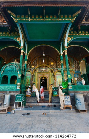 SRINAGAR, INDIA - JULY 22: Unidentified muslims enter a uniquely wooden mosque, Shah E Hamdan, a major tourist attraction, for evening prayers in Kashmir on July 22, 2009 in Srinagar, India - stock photo