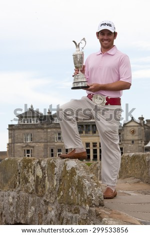 ST ANDREWS, SCOTLAND. July 19 2010: The Open Champion Louis OOSTHUIZEN from South Africa winner of the The Open Championship   on top of the Swilcan Bridge with the silver claret jug trophy.  - stock photo