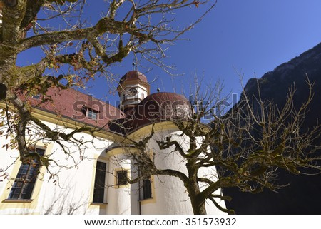 St Bartholomew chapel at lake Koenigssee in the Berchtesgaden National Park in front of the steep and approximately 1000 meters high cliff face with the lookout named Feuerpalven