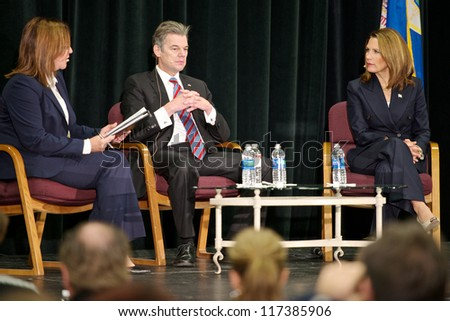 ST. CLOUD, UNITED STATES - OCTOBER 30: U.S. Rep. Michelle Bachmann and Democrat challenger Jim Graves listen to debate moderator Teresa Bohnen ask a question on October 30, 2012 in St. Cloud. - stock photo