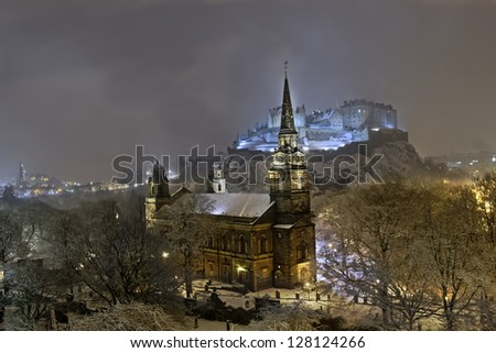 St. Cuthbert's church, Edinburgh Castle, and surrounding city skyline illuminated at night during winter snow fall.