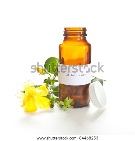 St. John's Wort capsules with a Hypericum perforatum plant on white. The label was made for the photo shoot, no copyright or brand name infringement issues. - stock photo