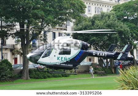 ST. LEONARDS-ON-SEA, ENGLAND - AUGUST 27, 2015: The Kent Air Ambulance takes off from Warrior Square Gardens while attending a medical emergency. The helicopter is a McDonnell Douglas MD902 Explorer. - stock photo