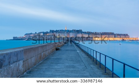 St Malo, Panorama Seaside View over the walled city Saint-Malo medieval pirate fortress and St Vincent Cathedral at Night in Summer under Blue Sky Blur Cloud, Brittany, France from lighthouse - stock photo