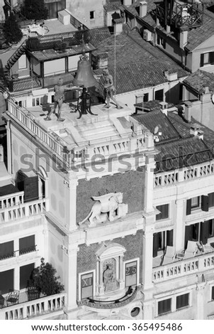St Mark's Clocktower with Winged Lion, Bell and Madonna with Child. A view from the Campanile tower at Piazza San Marco in Venice (Italy). Aged photo. Black and white. - stock photo