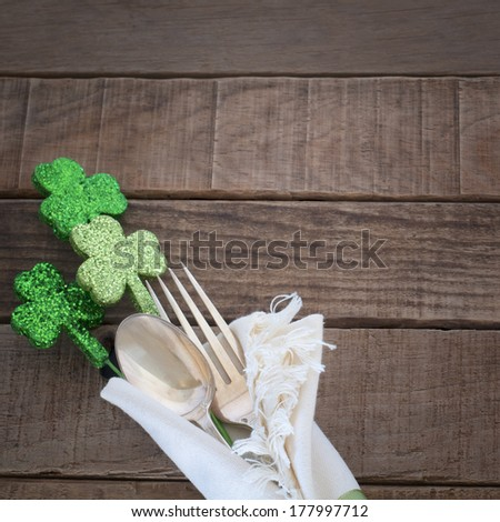 St. Patrick's Day green Shamrocks with fork, spoon, and napkin on rustic brown wood board background with room or space for copy, text, words.  Square - stock photo