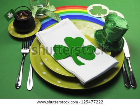 St Patrick's Day party table setting decorated with green polka dot plates, shamrocks, pot of gold and leprechaun hat with rainbow on green background. - stock photo