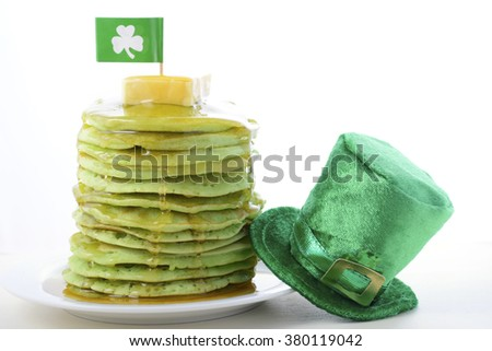 St Patricks Day green pancakes with drizzling syrup, shamrock flag and green leprechaun hat.  - stock photo