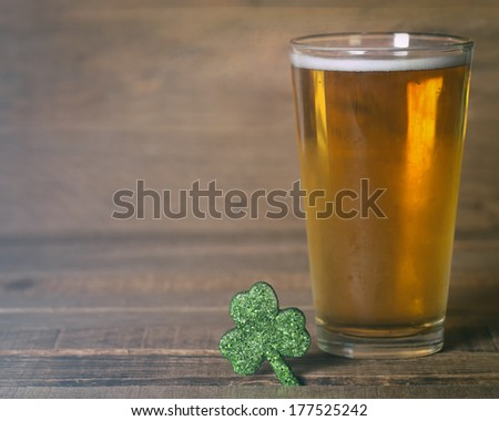 St. Patricks day green shamrock and frosty cold glass of beer on wood background with room or space for text, copy, words.  Vintage camera instagram treatment. - stock photo