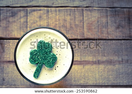 St. Patricks Day, Irish Shamrock Floating in Frothy Beer Mug on rustic wood board background with room or space for copy, text, your words.  Horizontal faded filter instagram, tint, dark and moody  - stock photo