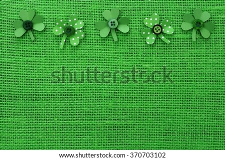 St Patricks Day top border of handmade paper shamrocks over a green burlap background - stock photo