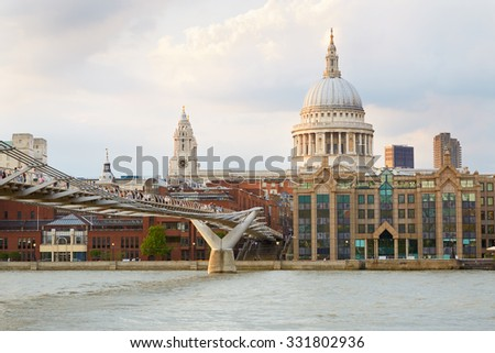 St Paul Cathedral and Millennium bridge with people in London afternoon, natural colors - stock photo