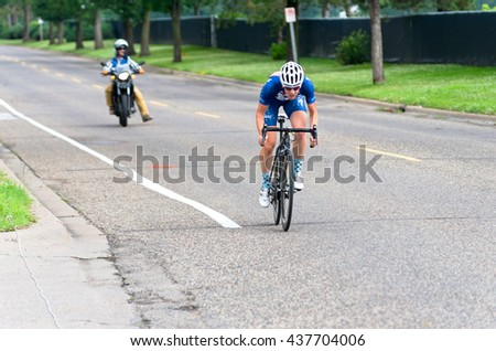 ST. PAUL, MINNESOTA - JUNE 15, 2016: The annual North Star Grand Prix pro cycling event begins with stage one time trial in St. Paul on June 15 as a competitor races to the finish line.  - stock photo
